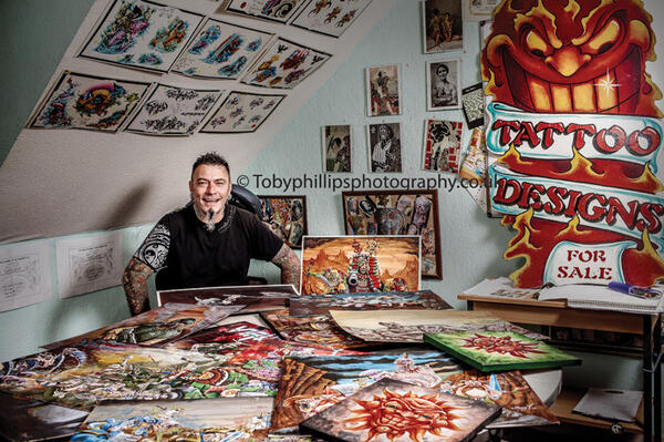 Danny Fuller with some of his colourful paintings